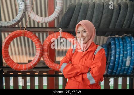Weibliche Mechanikerin in einem Schleier, der die Kamera mit anschaut Gekreuzte Hände, die vor einem Reifenständer stehen Eine Motorrad-Ersatzteilwerkstatt