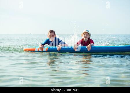 Zwei glückliche Geschwister Teenager Kinder in Neopren Anzüge spielen und Spaß mit supboard im Wasser in der Ostsee Stockfoto