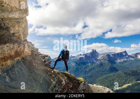 Junger Mann mit 22 Jahren auf dem gut ausgerüsteten Weg Astaldi (charakteristisch für farbige Felsen) an den Fussen von Tofane, Cortina d'Ampezzo, Dolomiten, Belluno, Venetien, Italien Stockfoto