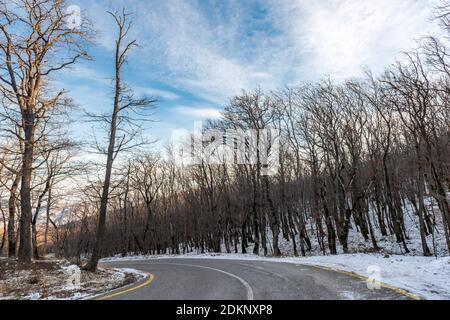 Rutschige kurvenreiche Straße in einem Winterbergwald