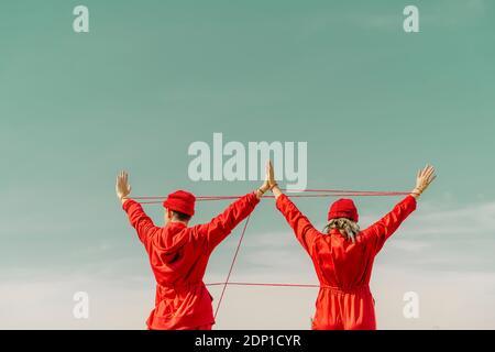Rückansicht eines jungen Paares mit roten Overalls und Hüten Durchführung mit roten String im Freien