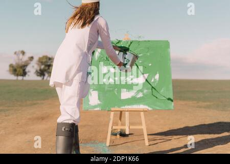 Junge Frau auf trockenem Feld, mit grüner Farbe auf Leinwand malen - Stockfoto