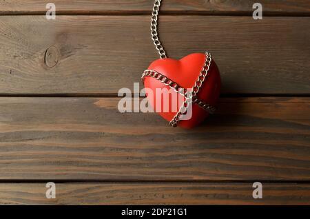 Herz und mit der Kette gesichert. Herz in Ketten auf dunklem Holzhintergrund. Rotes Herz und mit Ketten auf einem braunen rustikalen Tisch gesichert.