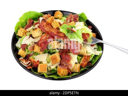 Bacon Caesar Salat mit Romaine-Salat und Parmesenkäse Serviert in einem schwarzen Gericht isoliert auf weißem Hintergrund