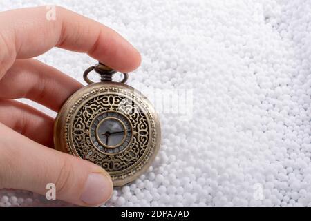 Zugeschnittenes Bild Der Hand Holding Antique Taschenuhr Auf Polystyrol-Perlen