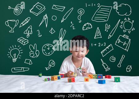 Asiatische Kind lernen, indem er mit seiner Phantasie über Schreibwaren liefert Schule Objekt Aktivitäten zum Lernen, Hand auf der grünen Tafel gezeichnet, Bildung zurück zur Schule Konzept Idee. Stockfoto
