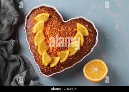 Hausgemachter Kuchen mit Orangen herzförmig bestreut mit farbigen Kokosflocken auf einem hellblauen Hintergrund. Nahaufnahme. Draufsicht