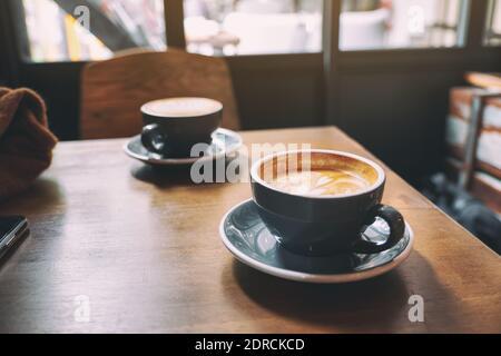 Nahaufnahme Bild von zwei blauen Tassen heißen Latte Kaffee auf Holztisch im Café Stockfoto