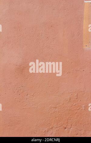 Vollformat abstrakter Hintergrund eines erodierenden äußeren Betonstein Wand mit rissiger und abblätternder rot lackierter Stuckputzoberfläche Textur