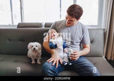 Junge kaukasische Vater Fütterung neugeborenes Baby mit Milch. Männlicher Elternteil mit Hund und gähnenden Kind auf den Händen. Authentischer Lifestyle lustig offen Moment. Single Dad Familienleben Konzept - Stockfoto