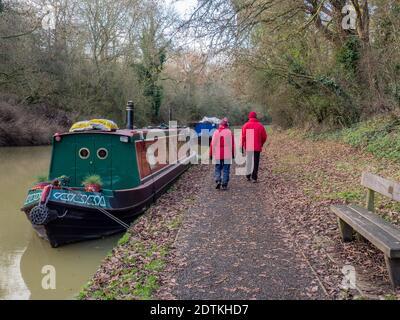 Ein Paar in passenden roten Mänteln bei einem Winterspaziergang am Kanal in Stoke Bruerne, Northamptonshire, Großbritannien