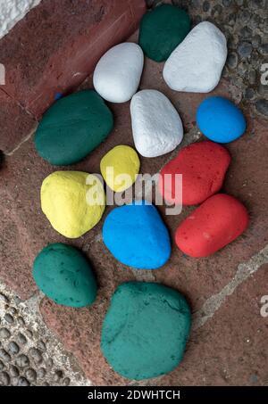 Farbsteine auf braunem Hintergrund; verschiedene Farben, gelb, weiß, blau, rot und grün