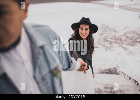 Mexikanischer hispanischer Mann in übergroßer Jeansjacke und Frau in hut Leder Biker Jacke küssen Umarmung lachend walking.groom Braut Hochzeit Ich liebe das Paar