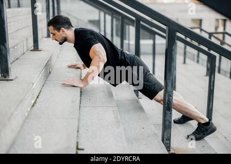 Gut gebauter junger Mann, der von der Treppe hoch schiebt. Seitenansicht. Ein sportlicher Mann mit schwarzen Haaren trägt schwarze Sportswear und Turnschuhe, die auf der Straße arbeiten