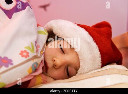 Ein kleines Mädchen (6 Jahre alt) Schlafend im Bett mit ihrem weihnachtshut an
