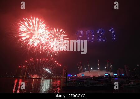 Feuerwerke und Drohnen beleuchten den Nachthimmel über dem O2 in London, da sie ein Lichtspektakel bilden, da Londons normales Silvesterfeuerwerk wegen der Coronavirus-Pandemie abgesagt wurde.