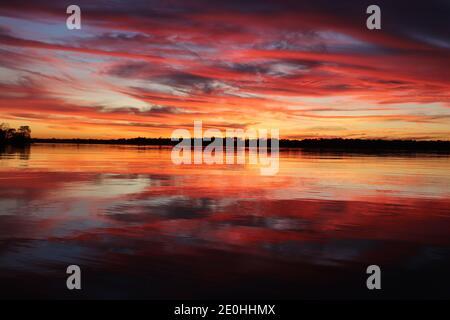 Sonnenuntergang mit Spiegelreflexen auf der Wasseroberfläche. Lebendige Farben von Rot und Gold wirbeln vom blauen Himmel bis zum ruhigen baumgesäumten Horizont.