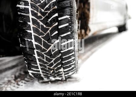 Neuer Winterreifen in einem silbernen Auto, der auf einer schneebedeckten Straße im Wald steht, ein sichtbares Profil mit Schnee.