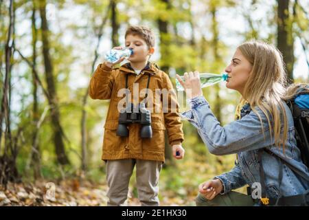 Glückliche Mutter und Sohn wandern im Wald. Sie sind Trinkwasser.