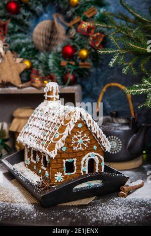 Festliche Weihnachten Styling von hausgemachten Lebkuchen Haus mit Zucker dekoriert Schneeflocken