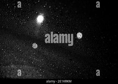 Glas mit Regentropfen vor dunklem Hintergrund.