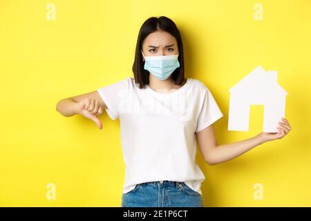 Covid-19 und Immobilienkonzept. Enttäuschte asiatische Frau in medizinische Maske, zeigt Daumen nach unten und Papierhaus Ausschnitt, stehen aufgeregt gegen gelb