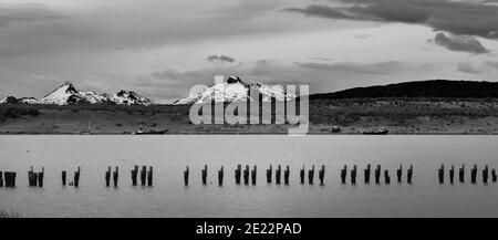 Schwarz-Weiß-Bild eines alten Steges mit den Anden in der Ferne bei Puerto Natales, Patagonien, Chile, Südamerika