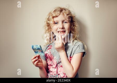 Kaukasische blonde Mädchen zeigt ihren fehlenden Zahn im Mund und hält Geld von Zahnfee. Stolzes Kind Kind zeigt verlorenen Zahn. Aufwachsen Bühne und