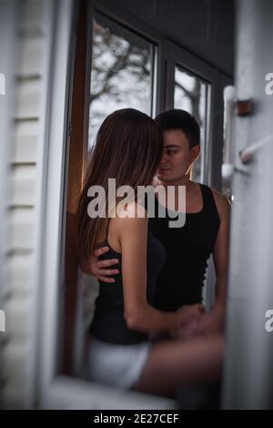 Ein liebevolles junges Paar umarmt sich im Fenster ihrer Balkonterrasse in der Wohnung. Der junge Mann lacht mit einer schönen Frau zu Hause. Liebhaber küssen, Pass Stockfoto