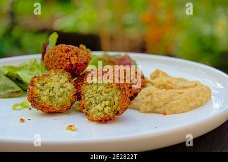 Download Preview drei Falafel-Kugeln, Haushälter und Salat auf einem Teller, mittelöstliches Essen. Selektiver Fokus