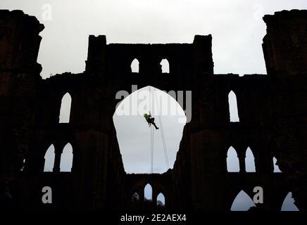 Der Steinmetz James Preston von SSH Conservation, abseils von Rievaulx Abbey in North Yorkshire als English Heritage bereitet sich auf die Durchführung von lebenswichtigen Naturschutzarbeiten vor. English Heritage beauftragt eine Untersuchung der Abtei Rievaulx in einem fünfjährigen Zyklus, um den Zustand der Abtei vom Boden bis zur Spitze der Struktur zu beurteilen.