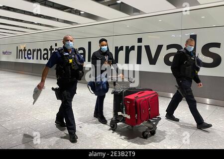 Ein Passagier geht mit Polizeibeamten, während er einen Trolley durch die Ankunftshalle von Terminal 5 am Londoner Flughafen Heathrow schiebt, nachdem er nach der Aufhängung der Reisekorridore in Großbritannien angekommen ist. Passagiere, die von einem beliebigen Ort außerhalb des Vereinigten Königreichs, Irlands, der Kanalinseln oder der Isle of man ankommen, müssen einen Nachweis über einen negativen Coronavirus-Test und eine Selbstisolierung für 10 Tage erhalten. Bilddatum: Montag, 18. Januar 2021.