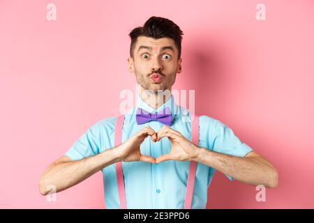Alles gute zum Valentinstag. Lustige junge Mann wartet auf Liebhaber Kuss, Pucker Lippen und zeigen Herz Zeichen, Ich liebe dich Geste, drücken Gefühle auf Datum, rosa