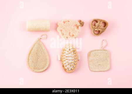 Bad-Accessoires, Naturlöffelschwamm, Holzbürste auf rosa Hintergrund. Zero Waste und plastikfreies Konzept, nachhaltiges Bad und Lifestyle