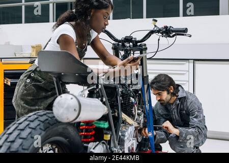Schwarze weibliche Mechaniker mit Tablet und männliche Techniker Reparatur Rad Von Motorrad mit Schraubendreher während der Arbeit in geräumigen Werkstatt zusammen