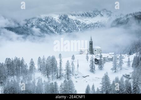 Italien, Venetien, Provinz Belluno, Rocca Pietore, Agordino, das Dorf Laste im Winter mit der Kirche von San Gottardo auf dem Hügel, Dolomiten Stockfoto
