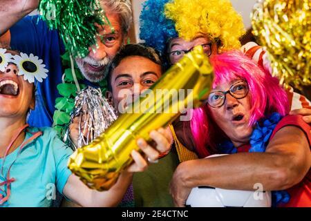 Verrückte Familie gemischte Altersgruppen feiern und genießen Sie das Fußballspiel Zusammen mit farbigen Kleidung des Teams - Gruppe von Die Menschen genießen die Sportwatch-Aktivität zu Hause und haben Spaß für Meisterschaftsturnier