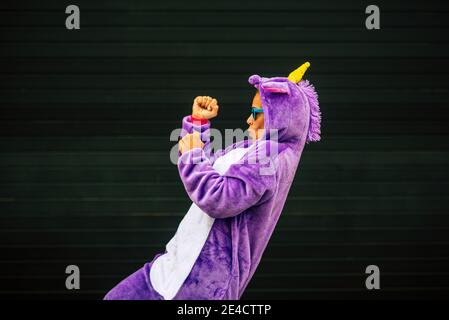 Verrückte Einhorn Maske Tanz mit lustigen Menschen - fröhlich glücklich Frau tanzt mit Karnevalskleid mit schwarzer Wand im Hintergrund - Spaß und Glück Konzept