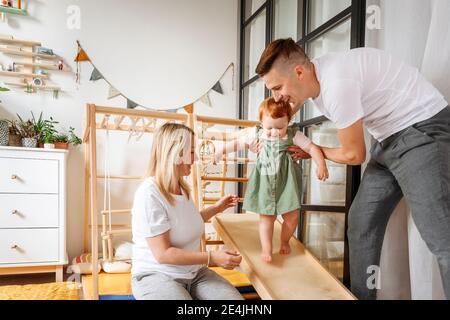 Eltern helfen Baby Tochter zu Hause gehen