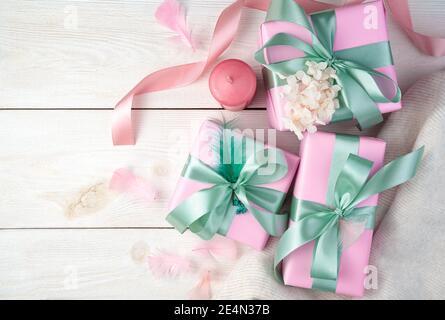 Eine festliche zarte Komposition mit Geschenkschachteln, einem Band, Kerzen und einem weißen Pullover auf hellem Holzhintergrund. Stockfoto
