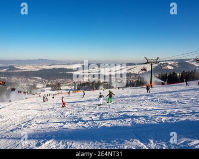Skipisten, Sessellifte, Skifahrer und Snowboarder im Skigebiet Bialka Tatrzanska in Polen im Winter. Schneekanonen in Aktion