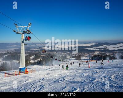 Skipiste, Sessellift, Skifahrer und Snowboarder im Skigebiet Bialka Tatrzanska in Polen im Winter. Schneekanonen in Aktion