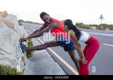 Fit afroamerikanischen Mann in Sportswear Stretching, während Frau ist Auf einer Küstenstraße stehen