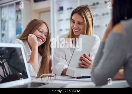 Ziemlich blonde kaukasische Frau mit jungen Dame in Business Casual Kleidung auf der Suche nach der Zwischenablage in Optiker-Center