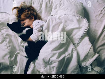 Mädchen spielt mit Katze in einem Bett