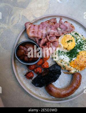 Englisches Frühstück mit Spiegeleiern, Speck, gebratenen Tomaten, gebratenen Pilzen, gebackenen Bohnen, Petersilie und Schweinewurst