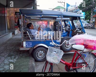 Ein Thai Tuk Tuk oder Taxifahrer ruht während Spielt mit seinem Handy, während er auf die Passagiere wartet Mit einem Fahrrad im Vordergrund