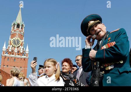 Zweiten Weltkrieg Veteran spricht auf einem Mobiltelefon, während seine Familie eine Militärparade auf dem Roten Platz in Moskau 9. Mai 2010 Uhren. NATO-Truppen werden über den roten Platz am Sonntag marschieren, da Russland den 65. Jahrestag des Sieges über Nazi-Deutschland, eine Geste der Freundschaft im Westen markiert die gewann Lob von Präsident Barack Obama aber wütend Kommunisten. REUTERS/Denis Sinyakov (Russland - Tags: militärische Politik Jahrestag) Stockfoto