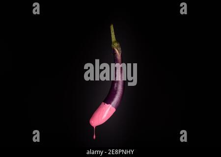 Aubergine isoliert schwimmend mit rosa tropfender Farbe. Schwarzer Hintergrund. Kreatives Food-Konzept