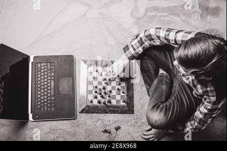 Kaukasischer Teenager Junge spielen Schach im grauen Teppich, Bildung, Aktivität und Hobby zu Hause Konzept, monochrom, Kopierraum, Draufsicht